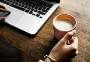 Woman's hand on a coffee cup at a dark wood desk with a laptop, ready to provide virtual assistant services.