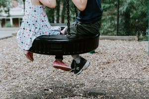 The feet and legs of a boy and girl sitting on a tire swing with house and trees in the distance