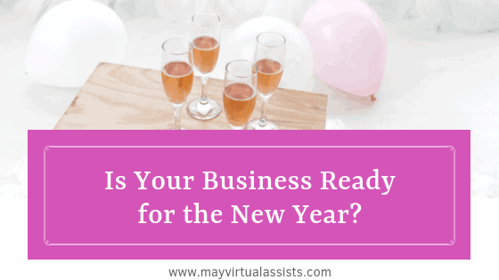 glasses of champagne on a wooden crate with balloons on the floor around and a magenta overlay with Is your Business ready for the new year? and mayvirtualassists.com