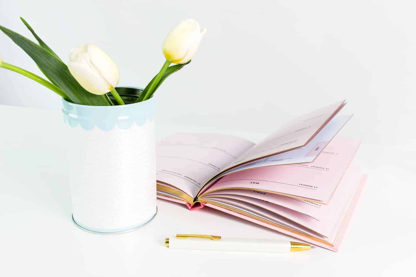 a vase with tulips and open planner