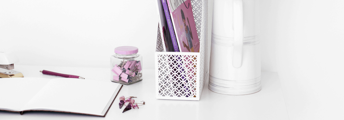 office supplies and a vase on a desk